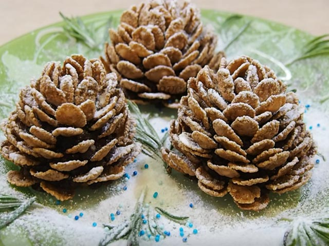 Десерт в виде шишек на тарелке с веточками розмарина и сахарной пудрой