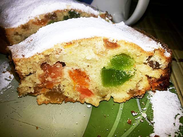 Кусочек рождественского пирога с цукатами и сухофруктами на тарелке